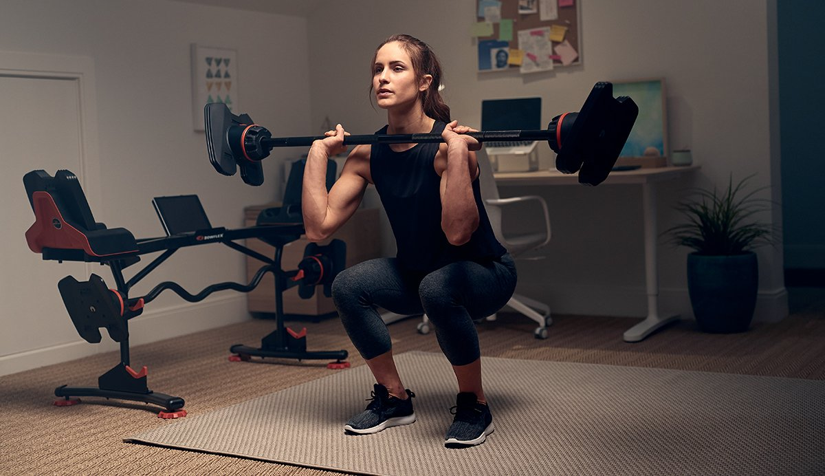 Woman doing a barbell squat exercise in a home-office