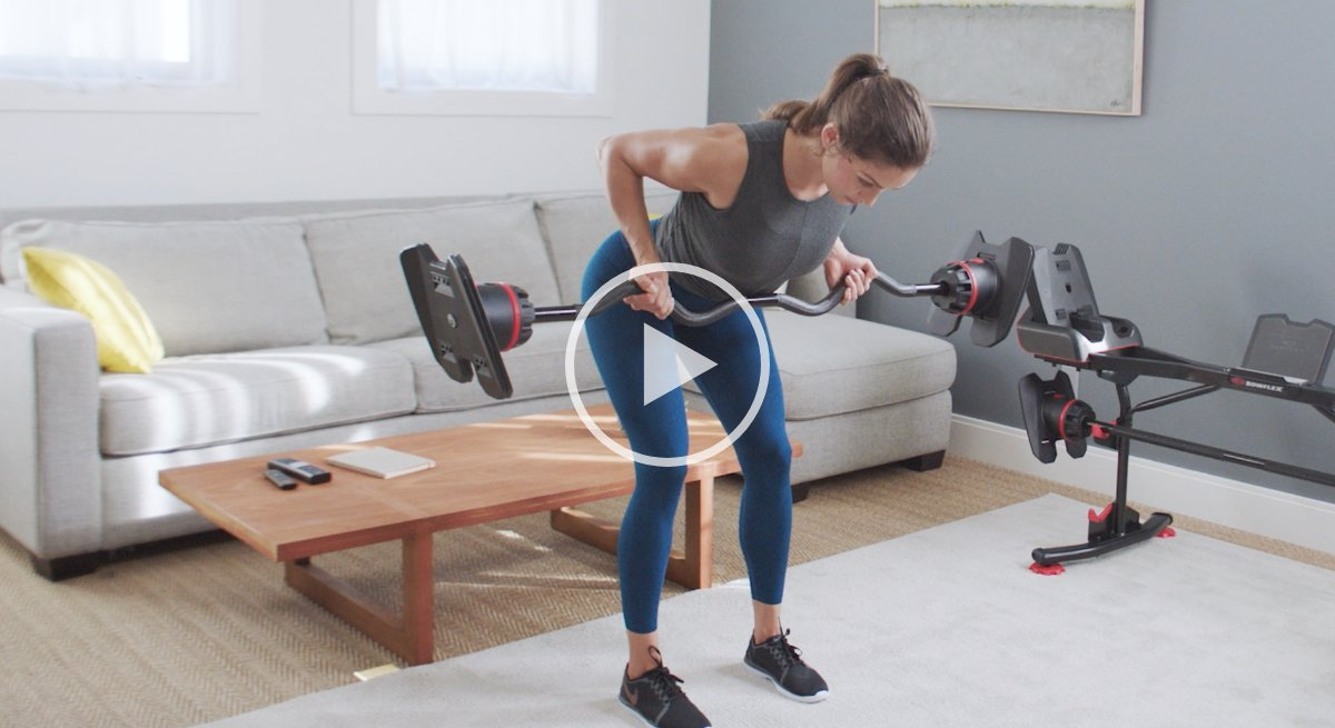 A woman working out with the SelectTech Adjustable Curl Bar