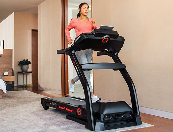 man running on a BXT216 Treadmill in a sunny room